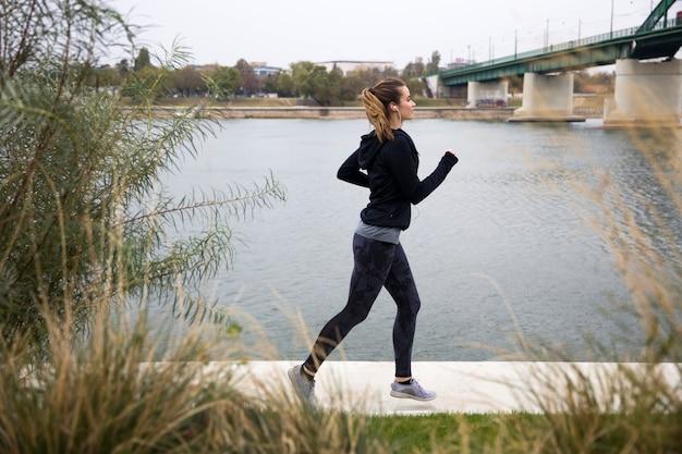 Female runner near river side