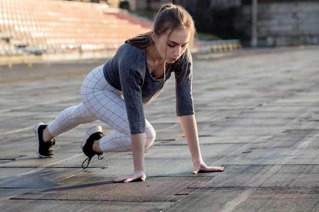 Женский бегун, протягивая ноги на беговой дорожке.