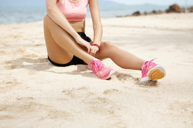 Female runner with beautiful legs wearing pink running shoes sitting on sandy beach, having small break after active running workout outdoors at the ocean.