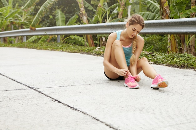 Female runner with blonde braid sitting on pavement, lacing her pink running shoes, getting ready for jogging workout outdoors.