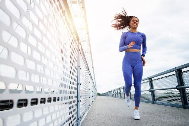 강한 몸매와 다리가 다리를 가로 질러 달리고 훈련하는 여성 주자.