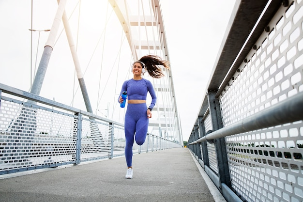 強い体と足で橋を渡って走り、トレーニングをしている女性ランナー。