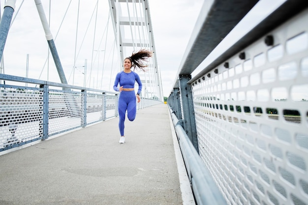 Female runner with strong body and legs running across the bridge and training