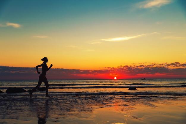 Женщина, бегущая вдоль морского побережья