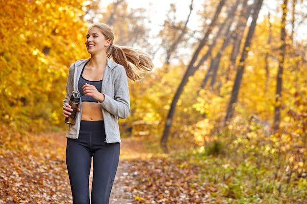 晴れた秋の天気で、スポーツ服を着て、森の中をジョギングしている女性。スポーツ、トレーニング、実行、幸福の概念