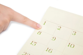 Female's finger showing date in a calendar on white background. number in the calendar