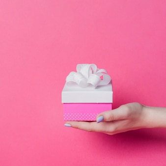 Female's hand holding box with white ribbon bow on pink background