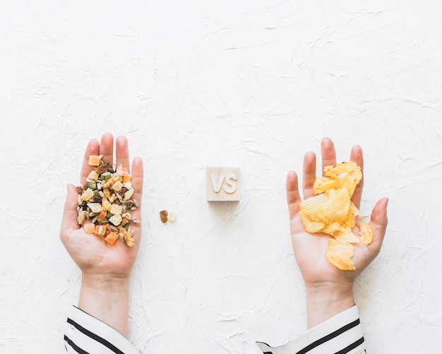 Female's hand holding dryfruits versus potatoes chips on textured backdrop