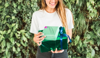 Female's hand holding green gift boxes