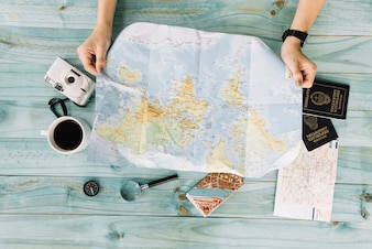 Female's hand holding map with camera; coffee; magnifying glass; map and passport on wooden plank