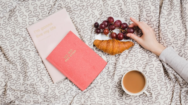 A female's hand holding red grapes with croissant; tea cup and books on tablecloth