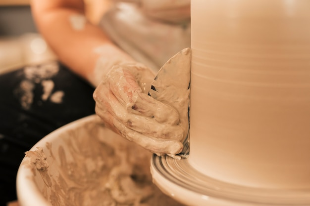 Female's hand smoothing out vase with flat tool on potters wheel