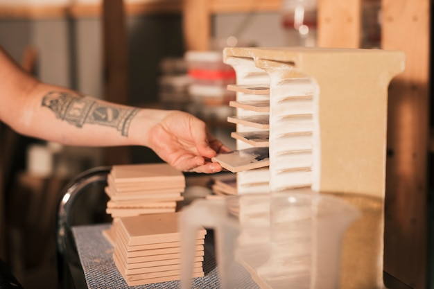 La mano della femmina che elimina le mattonelle organizzate dalla cremagliera Foto Gratuite