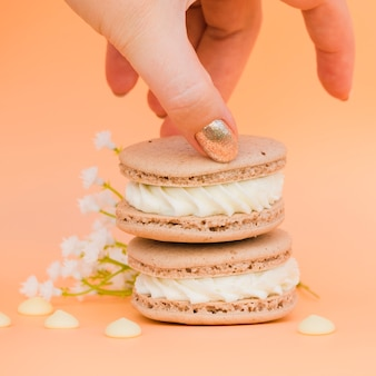 Female's hand with golden nail polish taking macaroon against colored backdrop