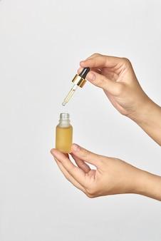 女性の手は、ライトグレーのテーブル、コピースペースに天然医療大麻エッセンシャルcbdオイルの小さなボトルとピペットを保持します。医療目的での大麻の使用。