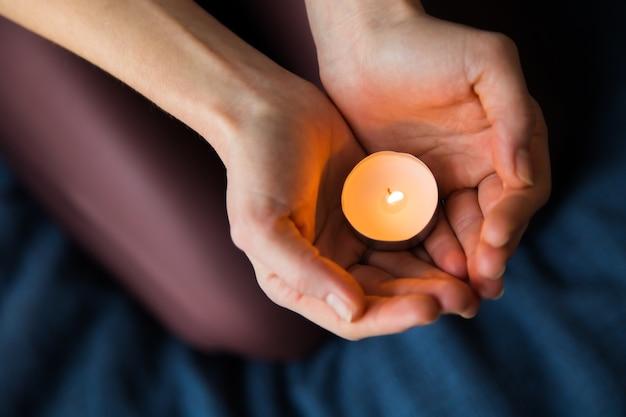 조명 된 촛불을 들고 여자의 손