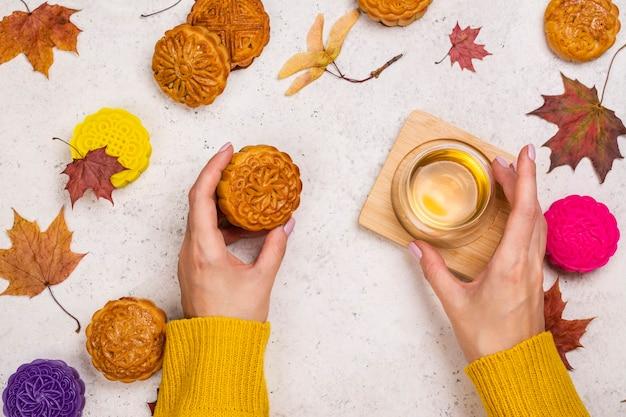 Женские руки держат чашку зеленого чая и лунный пирог yuebing. традиционный китайский торт юэбин - лунный пирог и кленовый лист на светлом каменном фоне. праздник середины осени