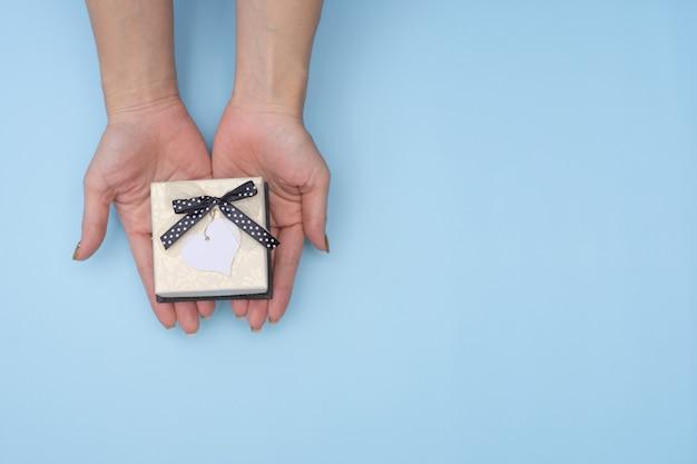 Женские руки, держа подарочную коробку с синим фоном.