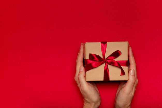 Female's hands holding gift box with red ribbon on red background.