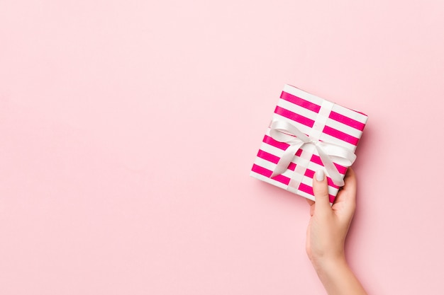 Female's hands holding striped gift box with colored ribbon on living coral.