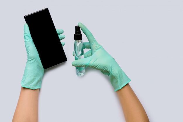 Руки женщины в латексных перчатках, протирая мобильный телефон с агентом обеззараживания алкоголя вид сверху на светло-сером фоне