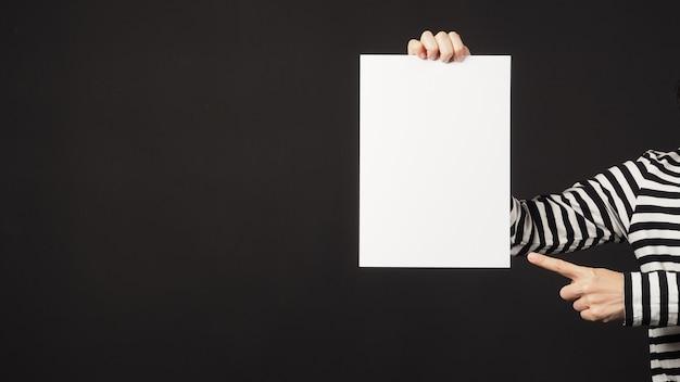 女性の手は空白の空のa4紙を保持し、黒の背景を指しています。女性は黒と白のストライプのtシャツを着ています。