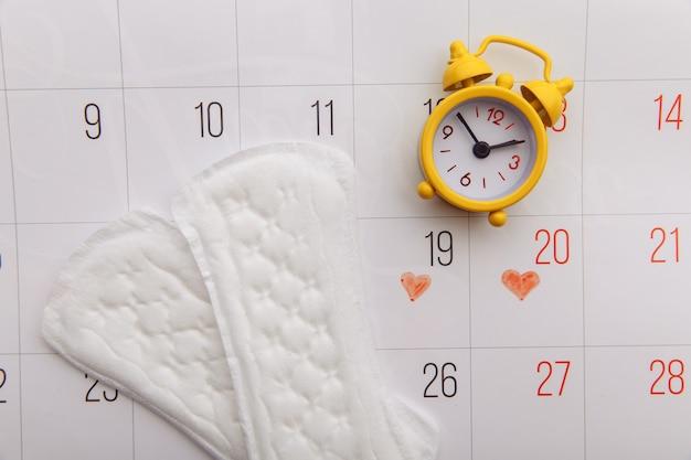 Концепция женского менструального цикла. менструальный календарь с гигиеническими прокладками и будильником.