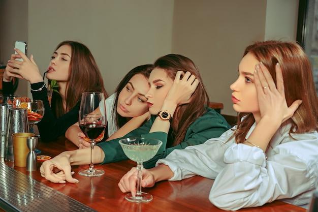 バーで飲み物を飲んでいる女性の悲しくて疲れた友人。彼らはカクテルを片手に木製のテーブルに座っています。彼らはカジュアルな服を着ています。