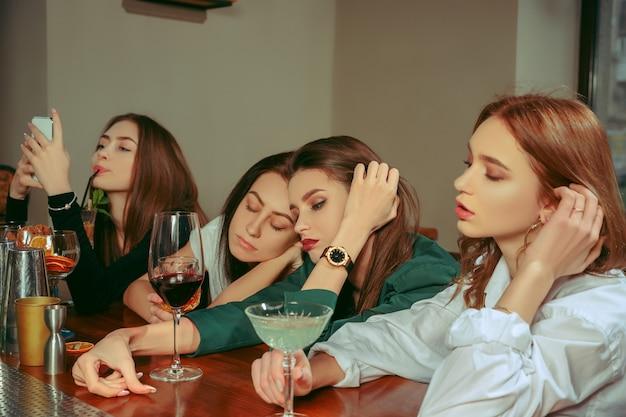 술집에서 술을 마시고있는 여성 슬프고 피곤한 친구. 그들은 칵테일과 함께 나무 테이블에 앉아 있습니다. 그들은 평상복을 입고 있습니다.