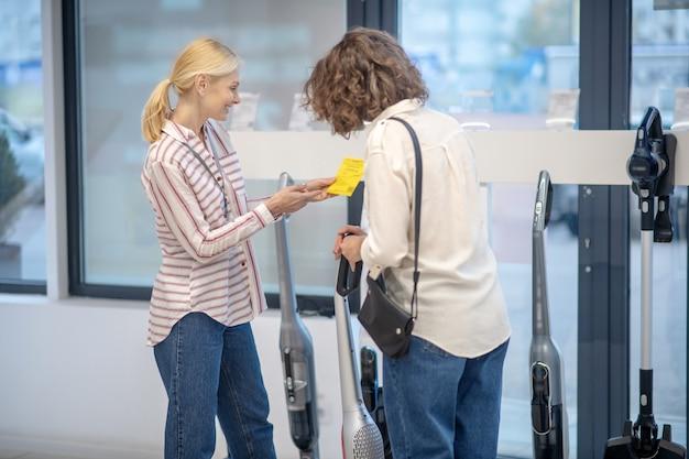 고객에게 새로운 장치를 보여주는 스트라이프 셔츠의 여성 판매 도우미