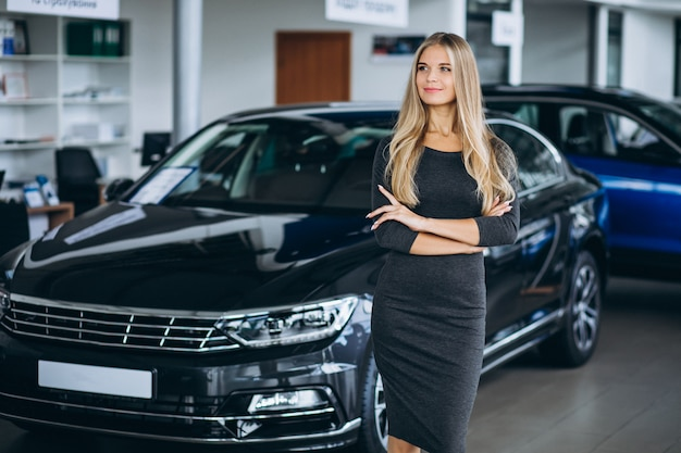 Female sales person in a car showroom by the car