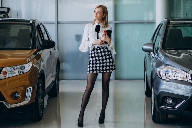 車のそばに立って車のショールームで女性営業担当者