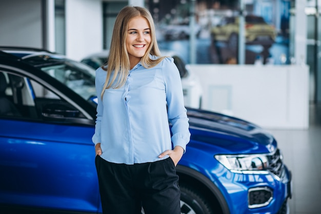 Female salesperson at a car showroom by the car