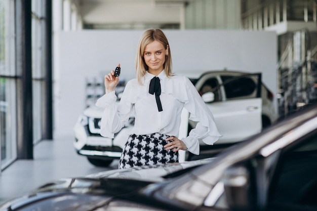 Female salesperson at a car showroom standing by the car
