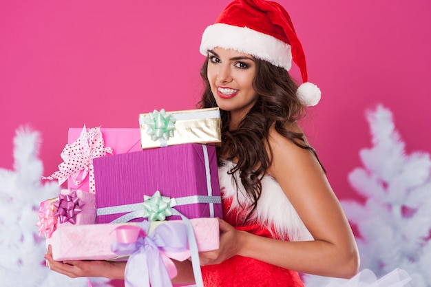 Female santa claus posing with gifts