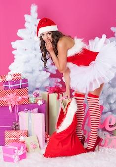 贈り物でポーズをとる女性のサンタクロース