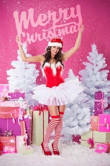 메리 크리스마스 글자와 함께 포즈를 취하는 여성 산타 클로스