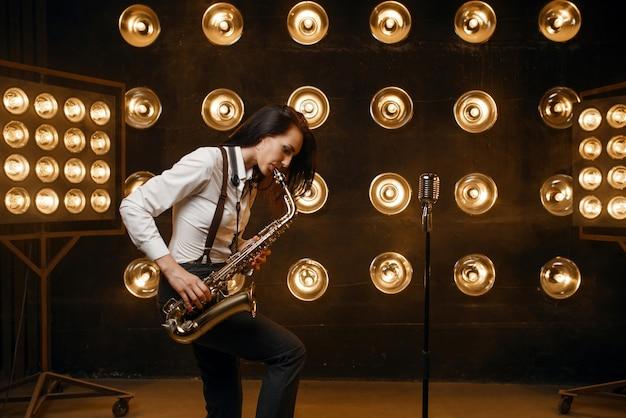 女性のサックス奏者は、スポット ライトを使ってステージでサックスを演奏します。現場で演奏するジャズパフォーマー