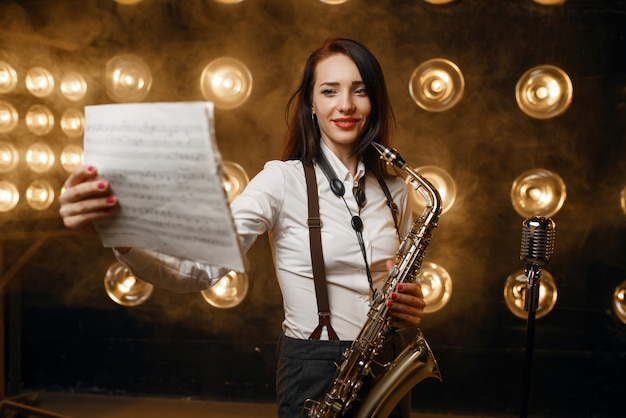 Female saxophonist with saxophone holds music book