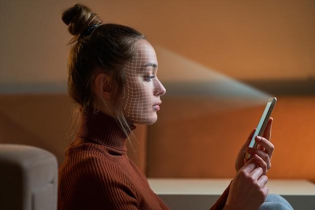 여성은 생체 인식을 위해 스마트 폰의 얼굴 인식 시스템을 사용하여 얼굴을 스캔합니다. 미래의 디지털 첨단 기술 및 id