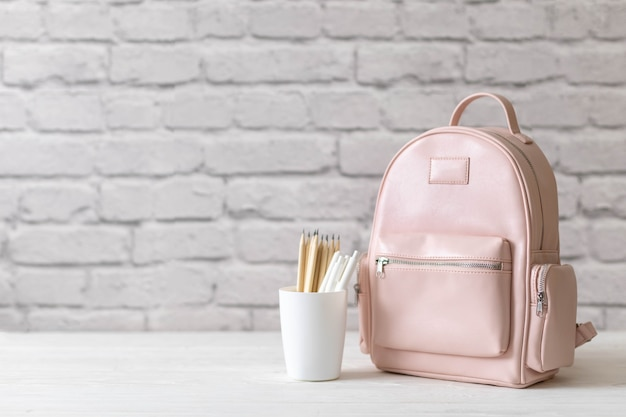 Female school backpack with stationery supplies on desk at white loft brick. concept of back to school