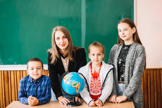 Female school teacher and students standing with globe