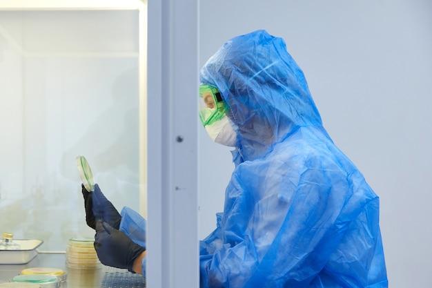 Женщина-исследователь в защитной форме и оборудовании работает с чашкой петри в лаборатории