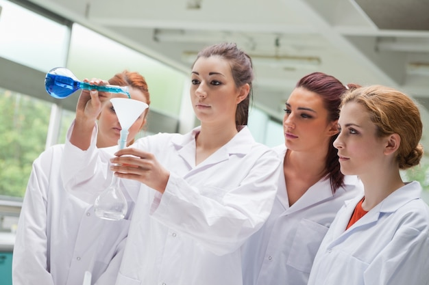 フラスコに液体を注ぐ女性科学学生