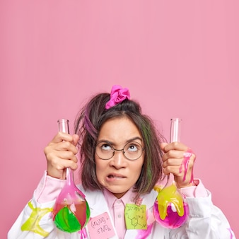 Female science worker bites lips holds samples of chemical liquid concentrated upwards busy conducting research wears spectacles and white coat on pink blank copy space