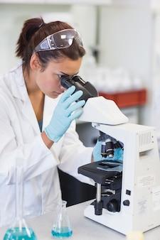 Female scientific researcher using microscope in lab