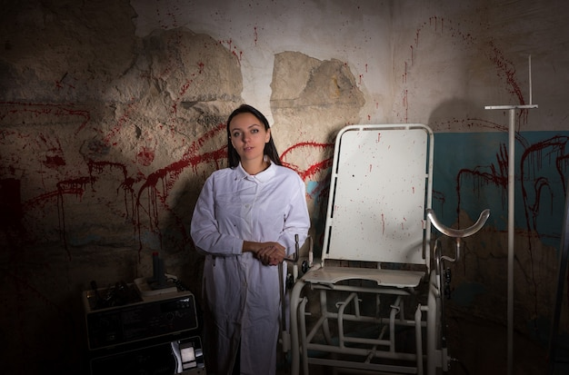 Female scientist in dungeon with bloody walls in a halloween horror concept