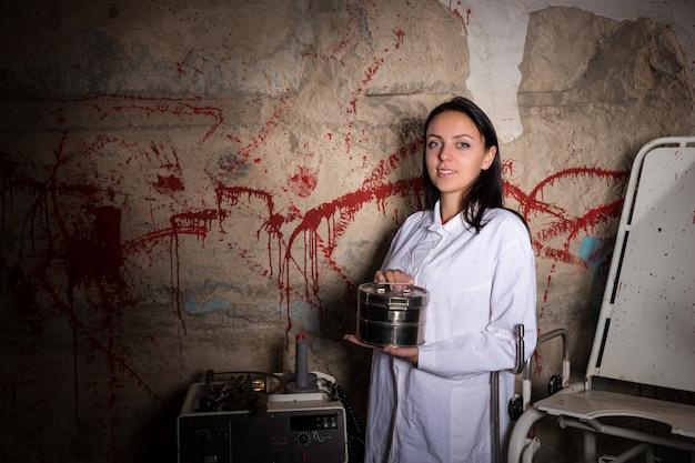 Женщина-ученый держит алюминиевый ящик перед забрызганной кровью стеной, концепция хэллоуина