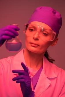 Женщина-ученый в кепке и защитных очках, работающая с химическими веществами в лаборатории, эффект красного света