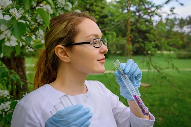 手袋をはめた女性科学者が庭で花びらを入れた試験管を持ち、香水、自然化粧品を作成